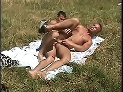 Hardcore gay action with two guys sucking and fucking in the middle of a field